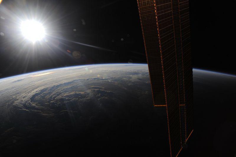 13. Над центром Атлантического океана, перед очередным изумительным закатом. Внизу в лучах заходящего солнца видны спирали урагана Эрл. Интересный взгляд на жизненную энергию нашего солнца. Солнечные лучи на левом борте станции и на урагане Эрл… эти два объекта собирают последние частички энергии перед погружением в темноту.