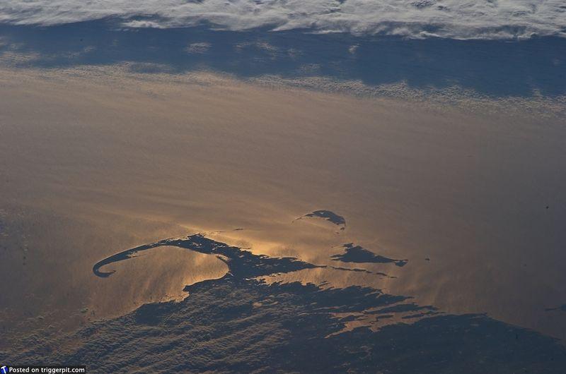17. Кейп Код, Массачусетс<br>Кейп Код, который местные жители называют просто Кейп, – остров и мыс в восточной части штата Массачусетс. Отражение солнца превращает Атлантический океан в золото, подсвечивая удивительный мыс. (NASA/ESA)