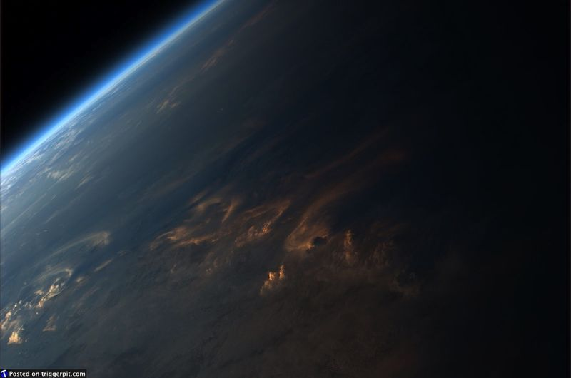 19. Закат над Западной Африкой<br>Этот снимок может сбить с толку. Мы видим прекрасное последнее мерцание заката. Однако на горизонте яркий свет. С этой точки обзора кажется, что здесь два источника света. Но солнце-то у нас одно. (NASA/ESA)